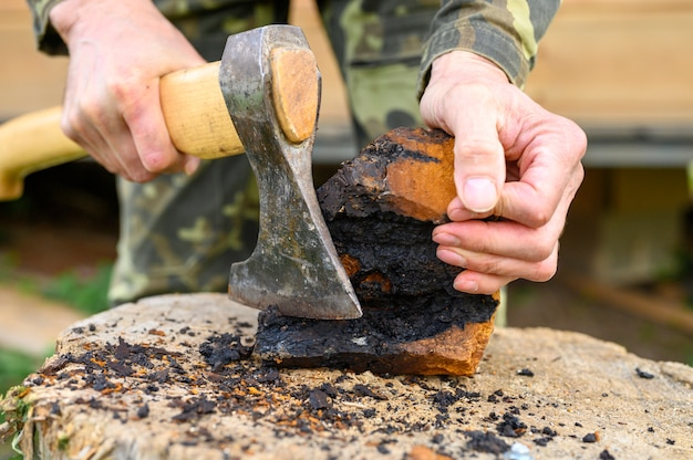 Le mani degli uomini con un'ascia puliscono il fungo chaga fungo di betulla all'aria aperta