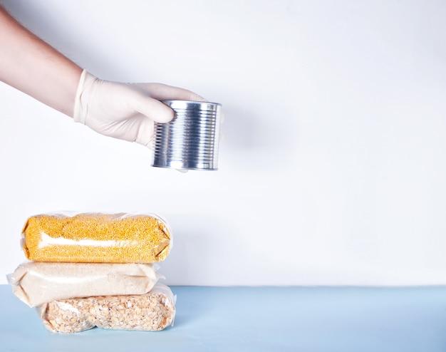 Le mani degli uomini con guanti di gomma danno lattina di cibo. donazione di cibo. consegna del cibo durante un'epidemia. consegna del prodotto senza contatto.