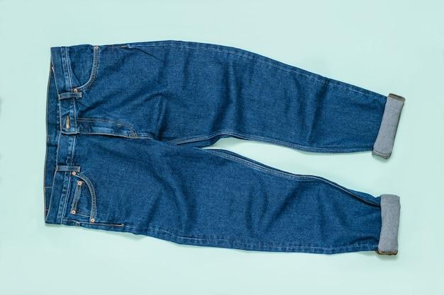 Jeans da uomo con polsini su sfondo blu. abbigliamento da uomo in denim alla moda. lay piatto. la vista dall'alto.