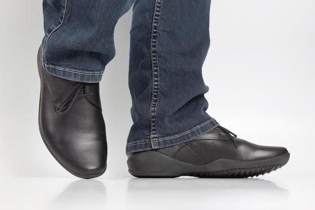 Piedini degli uomini in jeans e scarpe classiche nere su bianco