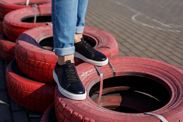 Sneakers o scarpe da uomo in vera pelle sul primo piano delle gambe degli uomini.