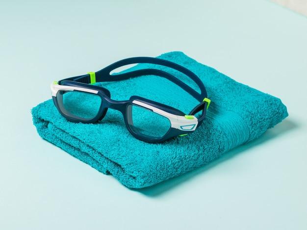 Occhialini da nuoto da uomo su un asciugamano ben piegato sul blu. accessori per il nuoto in piscina.