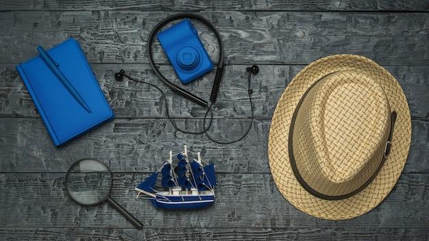 Kit da viaggio da uomo su un tavolo di legno nero. il concetto di pianificazione del viaggio.