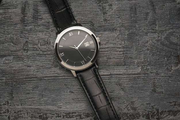 Orologio da uomo con lancette su fondo in legno. un accessorio da uomo alla moda e alla moda.