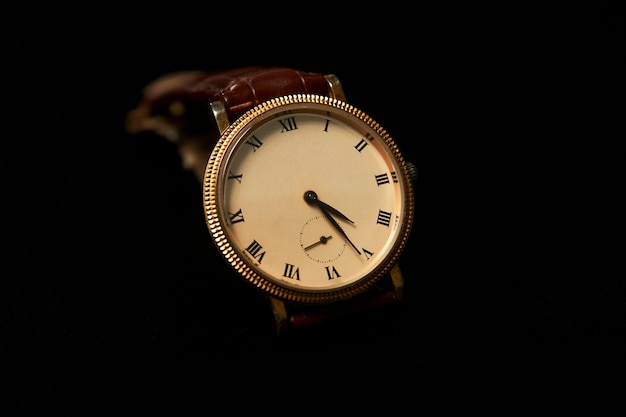 Orologio da polso da uomo su sfondo scuro, primo piano. orologio da polso di lusso in oro con cinturino in pelle marrone