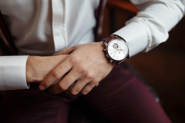 Orologio da polso da uomo, l'uomo sta guardando l'ora. orologio dell'uomo d'affari, uomo d'affari che controlla tempo sul suo orologio. mani dello sposo in un vestito che regola l'orologio da polso, accessori per lo sposo