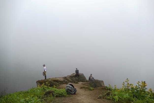 Uomini seduti su una scogliera in una valle che guardano la strada nebbiosa dei fiori