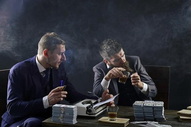 Uomini seduti a tavola con pile di soldi e macchina da scrivere concetto di affari illegali uomini d'affari che discutono affare illegale mentre bevono e fumano sfondo scuro società impegnata in affari illegali