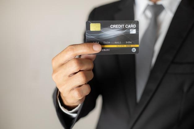 Gli uomini tirano fuori la carta di credito dalla tasca della tuta.