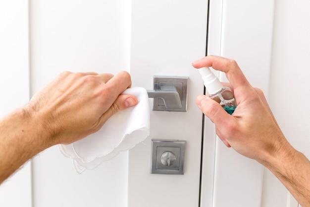 Gli uomini usano la carta alcolica per tenere la maniglia della porta per prevenire l'infezione e l'epidemia di virus covid 19. evita che il covid tocchi la porta.