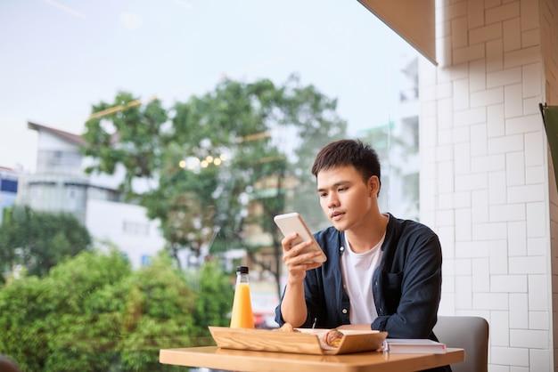 Gli uomini usano il telefono all'ora del tè, utilizzando lo smartphone mobile, lo stile di vita di internet delle cose con comunicazione wireless e internet con lo smartphone.