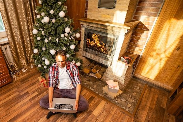 Uomini che usano il laptop in una vecchia casa di legno durante le vacanze di natale
