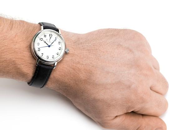 Un uomo che indossa un orologio con cinturino in pelle nera su uno sfondo bianco.
