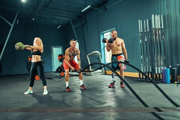 Uomini con la corda da battaglia nel fitness di allenamento funzionale in palestra