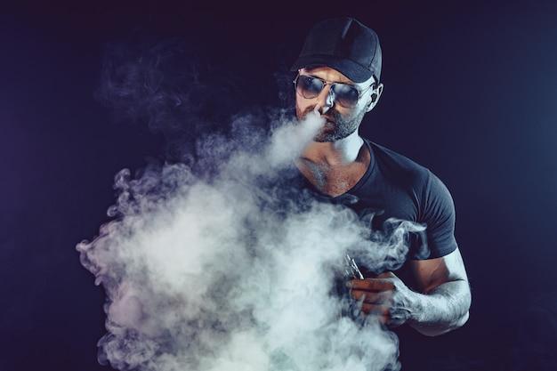 Uomini con la barba in occhiali da sole che svapano e rilascia una nuvola di vapore