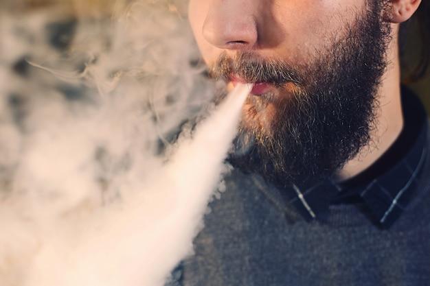 Uomini con la barba che svapano e rilascia una nuvola di vapore