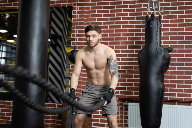 Uomini con corde da combattimento con funi da combattimento si esercitano nella palestra fitness. crossfit.