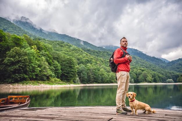 Uomini con un cane in piedi sul molo sul lago