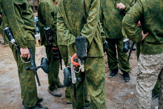 Uomini con le pistole che giocano a paintball. all'aperto