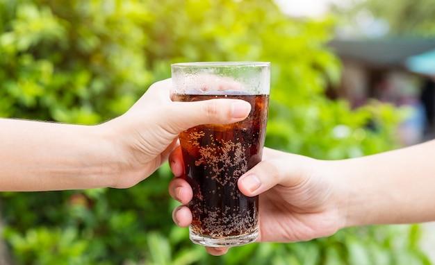 Mano di uomini e donne che dà un bicchiere di cola. bicchiere di cola, bibite con ghiaccio, innamorato o amico