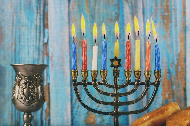 Menorah con candele accese colorate e bicchiere di vino