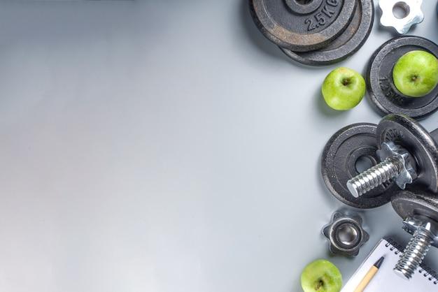Sfondo di fitness uomo con manubri in ferro scuro, scarpe da ginnastica, cuffie, mele gren e bottiglia d'acqua. su sfondo grigio vista dall'alto lo spazio della copia