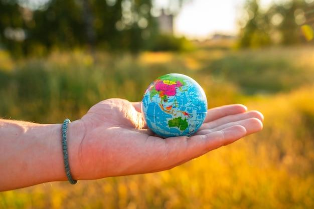 Le mani degli uomini tengono un globo al tramonto nel parco il concetto di protezione ambientale