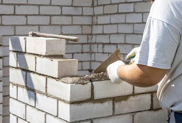 Le mani degli uomini posano i mattoni sulla ricostruzione della casa