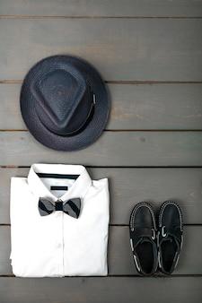 Abito da uomo su fondo in legno, vestiti di moda per bambini, fedora grigio, camicia bianca, scarpe da barca per ragazzo, vista dall'alto, piatto laico, copia spazio.