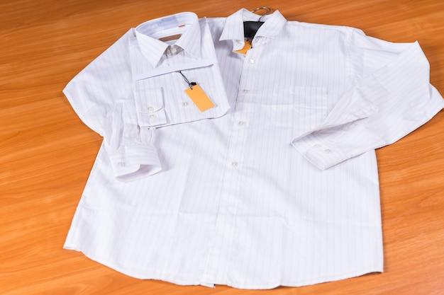 Camicia bianca da uomo distesa su una superficie di legno, con camicia identica piegata con etichetta attaccata su sfondo di legno