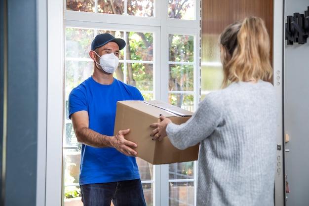 Mensajero con mascarilla indica un paquete a una mujer en su casa