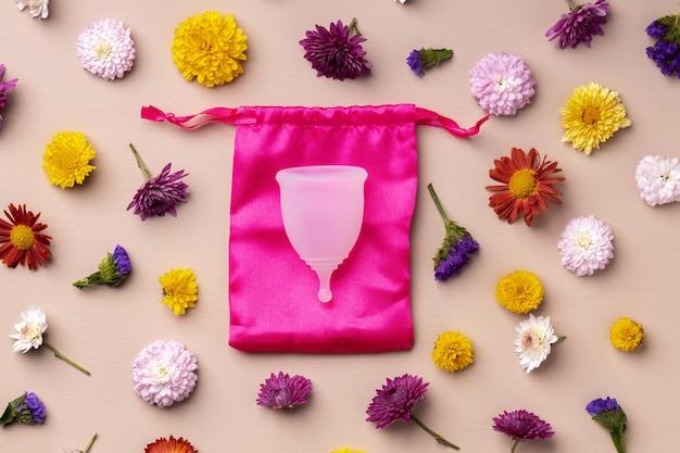 Coppetta mestruale su vista dall'alto di sfondo motivo floreale, copia dello spazio