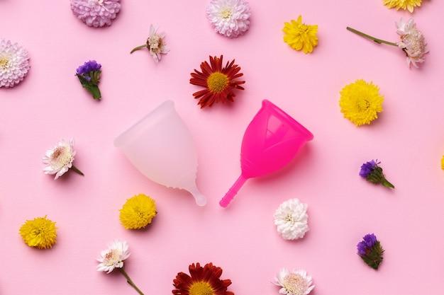 Coppetta mestruale sulla vista dall'alto di sfondo motivo floreale