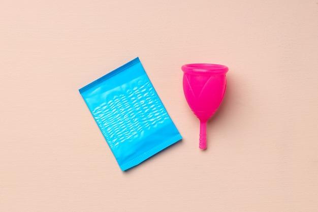 Coppetta mestruale e tampone igienico su sfondo di carta vista dall'alto
