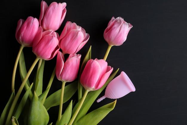 Coppetta mestruale e tulipani rosa su sfondo nero. la salute delle donne.