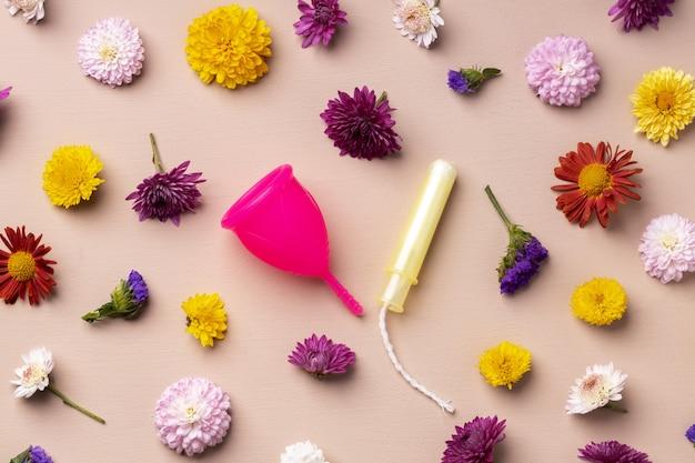 Coppetta mestruale e tamponi su sfondo motivo floreale