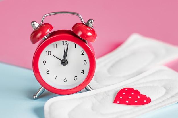 Cuscinetti mestruali, sveglia rossa su sfondo rosa. concetto di periodo mestruale. concetto di ritardo mestruale