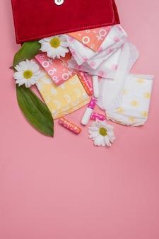 Tamponi mestruali e assorbenti in borsa per cosmetici. ciclo mestruale. igiene e protezione