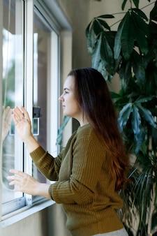 Salute mentale, stress, depressione durante la quarantena, blocco del coronavirus covid 19, giovane donna solitaria che guarda alla finestra, emozioni negative e concetto di salute mentale, libertà voluta