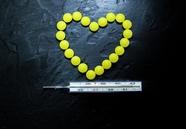 Termometro a mercurio con temperatura 36,6. persona sana. pillole a forma di cuore sullo sfondo. sistema cardiovascolare sano. concetto di virus.