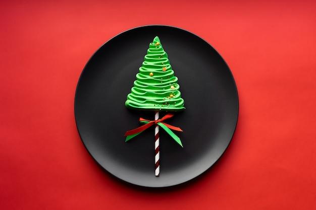 Albero di natale merengue su un piatto nero. sfondo rosso di natale.