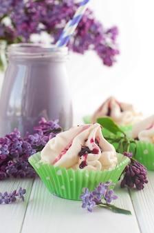 Torta di meringa vicino a frappè di mirtilli e fiori lilla