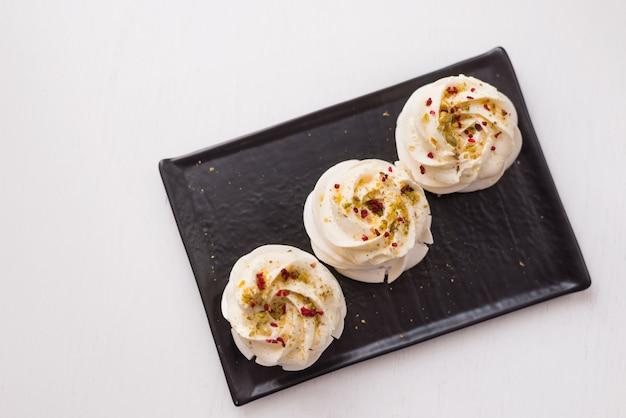Torte di meringa su un piatto nero. dessert pavlova su uno sfondo bianco. la vista dall'alto.