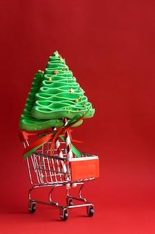 Albero di natale della meringa in un carrello della spesa. dolci natalizi.