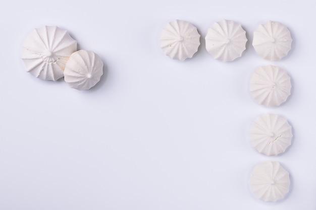 Biscotto di meringa su sfondo bianco, per sfondi o texture, copia dello spazio.