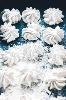 Biscotti di meringa su sfondo blu. sfondo di meringa. chicche di pasticceria