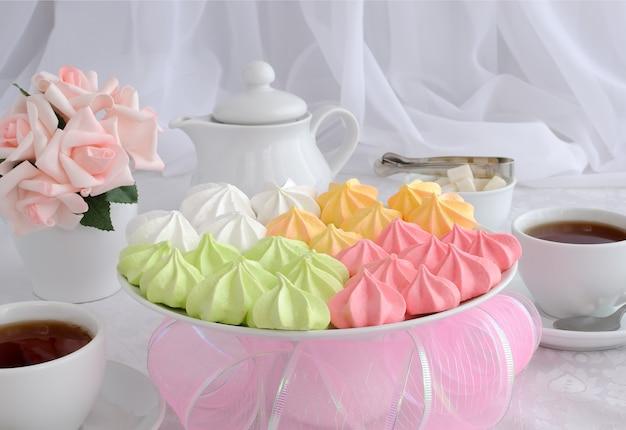 Biscotti di meringa di diversi colori su un piatto con una tazza di caffè