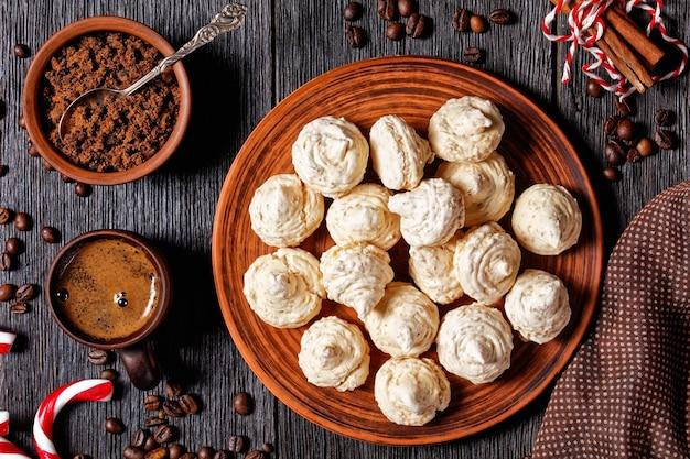 Biscotti di meringa serviti su un piatto con canna da zucchero natalizia, tazze di caffè, chicchi di caffè, zucchero di canna e bastoncini di cannella su uno sfondo di legno scuro, vista dall'alto, primo piano