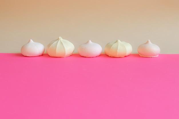 Meringa in fila. piccole torte di meringa su sfondo rosa brillante. sfondo delicato con i dolci.