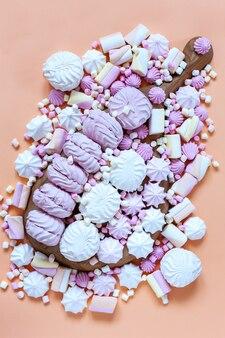 Meringa e varietà marshmallows charcuterie board su sfondo rosa. primo piano, vista dall'alto.